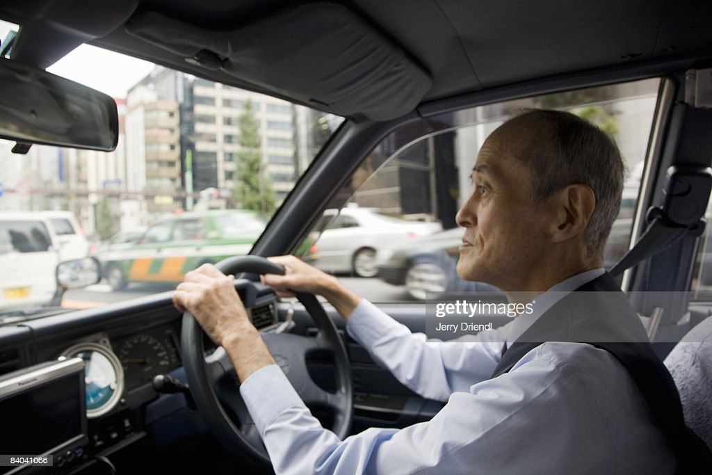 A taxi driver operating his vehicle : Stock Photo
