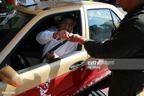 A taxi driver pays a Petroleos Mexicanos employee after fueling at the company's gas station in Mexico City Mexico on Wednesday Dec 28 2016 Mexico...