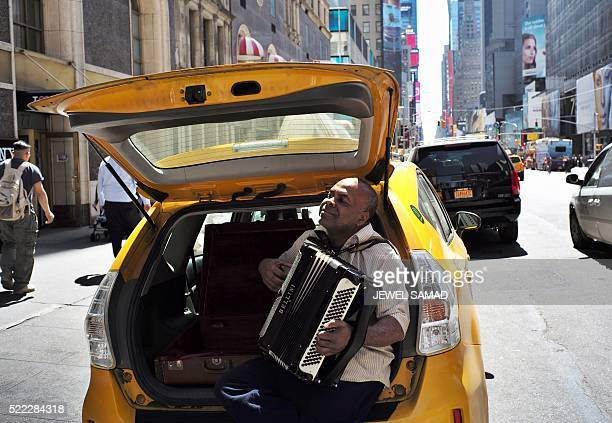 A taxi driver plays an accordion as he takes a break along a street in New York on April 18 2016 / AFP / Jewel SAMAD