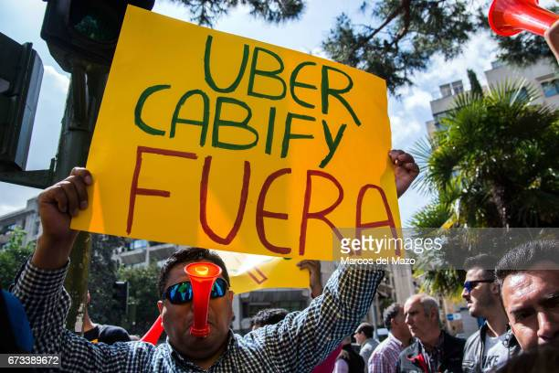 A taxi driver protesting with a placard during a demonstration against private transportation services such us Uber and Cabify