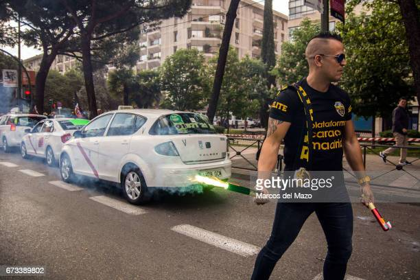 A taxi driver protesting with flares during a demonstration against private transportation services such us Uber and Cabify
