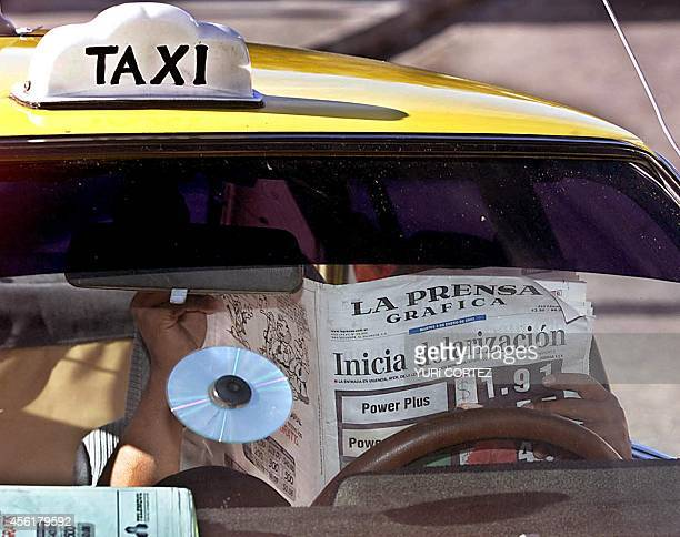 A taxi driver reads a newspaper with headlines about the newlylaunched dollar system 02 January 2001 in San Salvador The US dollar became legal...