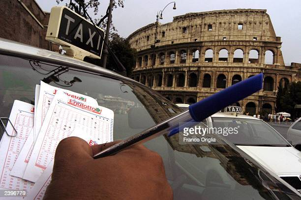 A taxi driver selects numbers to play Italy's main lottery known as SuperEnaLotto while in front of the Colosseum August 13 2003 in Rome Italy The...