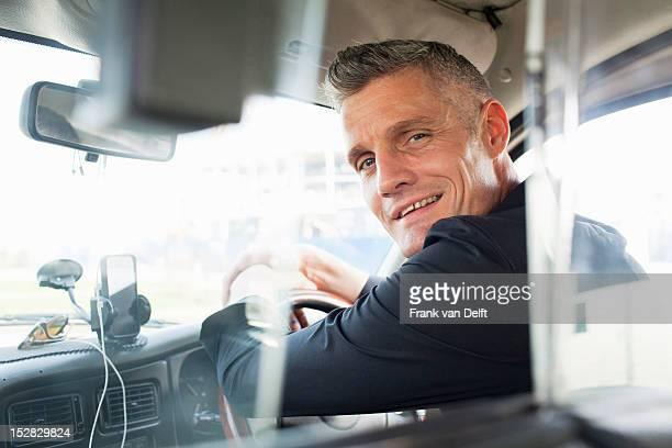 taxi driver sitting at steering wheel - taxi foto e immagini stock