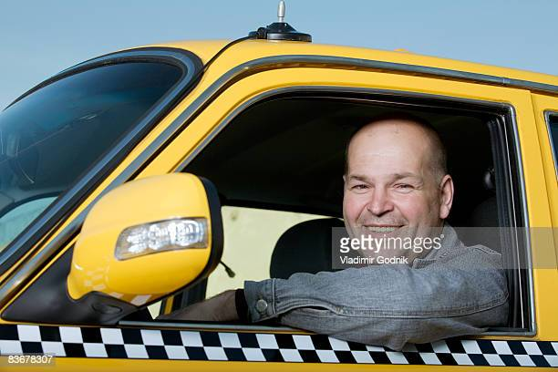 a taxi driver sitting in his car and smiling - taxi driver stock photos and pictures