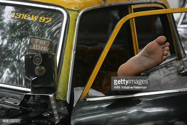 Taxi driver takes a nap in his vehicle, India