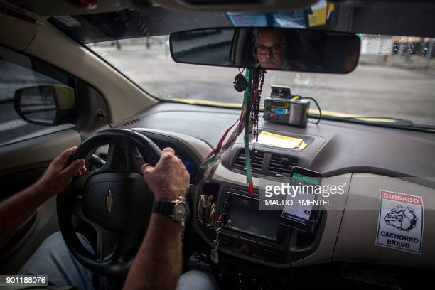 Taxi driver Tarcio Barbosa works with the Brazilian App for ridesharing 99 Taxi in Rio de Janeiro Brazil on January 4 2018 Chinese ridehailing giant...