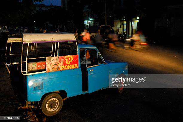 A taxi driver waits for a fare at an intersection in the evening in Mandalay Myanmar These small blue ancient Mazda trucks are a common sight around...