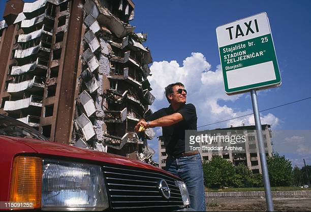 A taxi driver washes his car beside bomb damaged buildings in the suburbs of Sarajevo after the end of the war