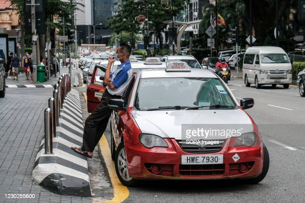 Taxi driver wearing a face mask waits for a passenger outside the Pavillion shopping mall. Malaysia has reported 2,018 new cases of Coronavirus today...