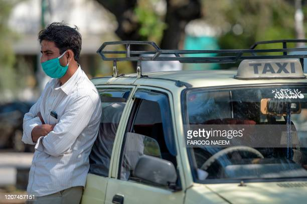 Taxi driver wearing a facemask amid concerns over the spread of the COVID-19 novel coronavirus waits for a customer outside a hospital in Islamabad...