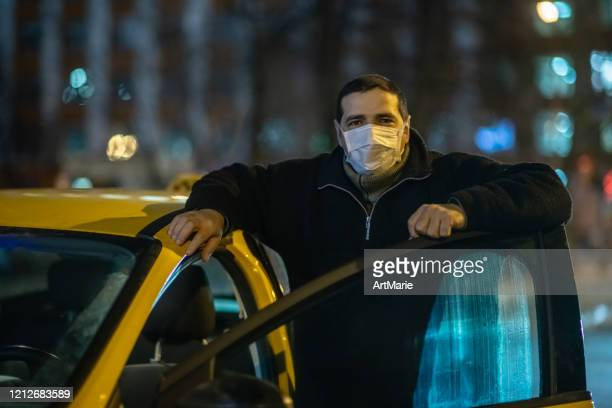 taxi driver wearing protective medical mask on a city street at night - driving mask stock pictures, royalty-free photos & images