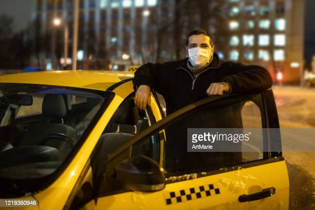 taxi driver wearing protective medical mask on a city street at night - essential workers stock pictures, royalty-free photos & images
