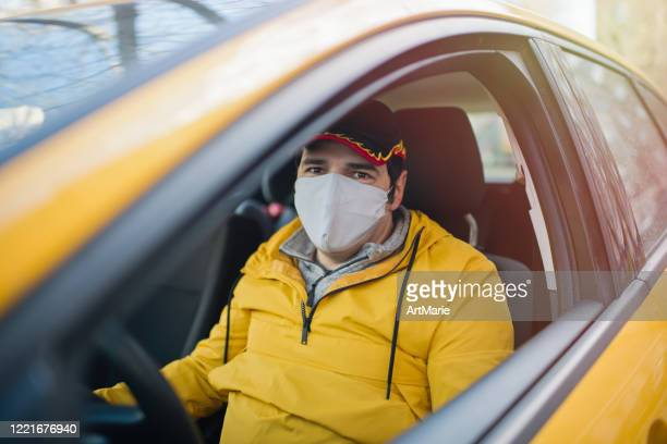 taxi driver wearing protective medical mask parked on a city street during an illness epidemic and waiting for his passanger - taxi driver stock pictures, royalty-free photos & images
