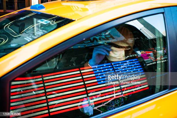 A taxi driver wears a face mask and gloves as he drives down Times Square on March 26 2020 in New York City Most cabdrivers are fearful of being...