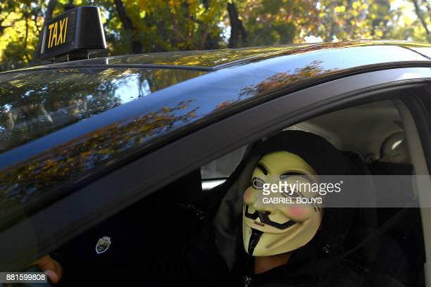 A taxi driver wears a Guy Fawkes mask during a taxi drivers demonstration against the competition from rival transport companies Uber and Cabify in...