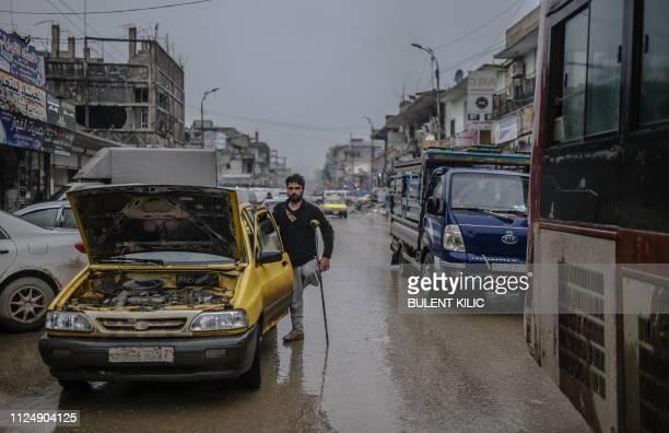 Taxi driver who lost his leg stands next to his vehicle on Tal-Abyad avenue in the northern Syrian city of Raqa on February 14, 2019. - In 2014,...