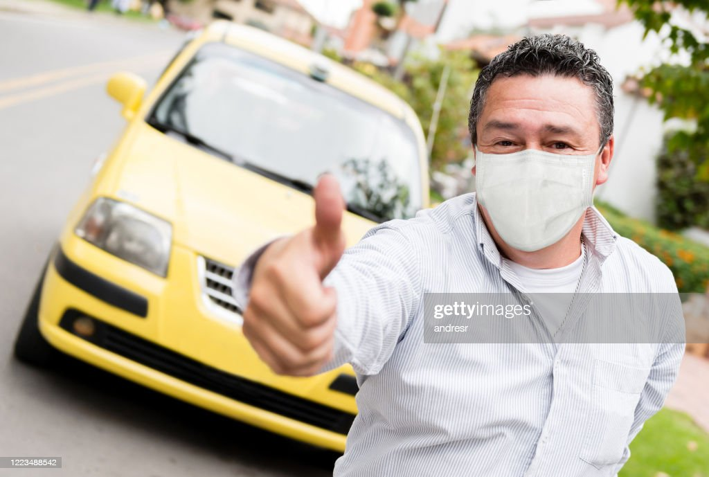 Taxi driver with thumbs up and wearing a facemask : Stock Photo