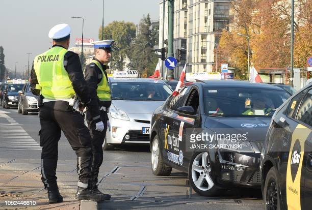 Policemen stand guard as taxi drivers take part in a goslow protest against the competition from companies without official licenses on October 18...