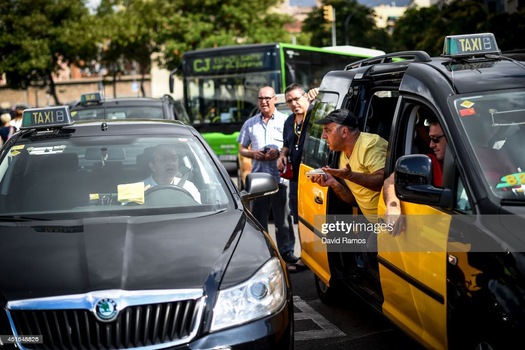 Taxi drivers argue with a taxi driver who was working at Barcelona Sants Train Station during a 24 hours strike against smart phone App 'Uber' on July 1, 2014 in Barcelona, Spain. Taxi drivers in main cities strike over unlicensed car-hailing services. Drivers say that is a lack of regulation behind the new app.