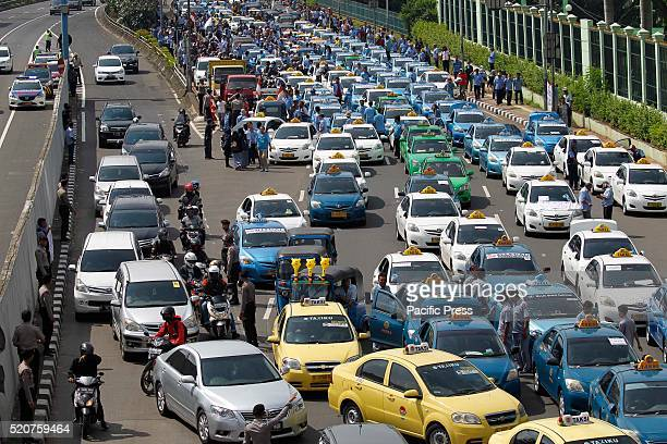 Taxi drivers block the main road during a protest rally to demand the government to prohibit ridehailing apps
