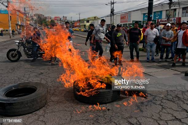 Taxi drivers burn tires as they block a road to protest against Ecuadorean President Lenin Moreno's government economic policies regarding the...