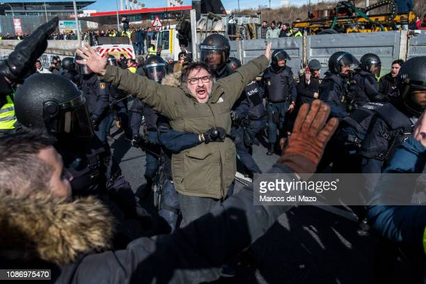 Taxi drivers clashing with riot police protesting against transport services such as Uber and Cabify as tourism exhibition FITUR starts