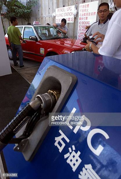 Taxi drivers clean their vehicles as they wait their turn to fillup with Auto LPG 30 June 2000 in Hong Kong where Caltex opened the first...