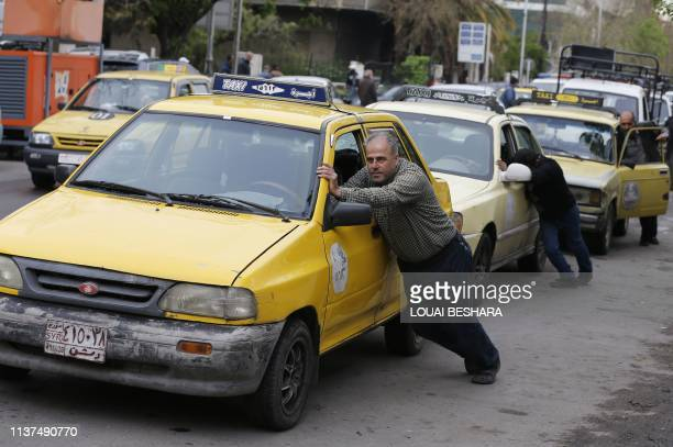 Taxi drivers push their cars that ran out of gasoline to a petrol station in the Syrian capital Damascus on April 16 2019 Syria adopted new measures...