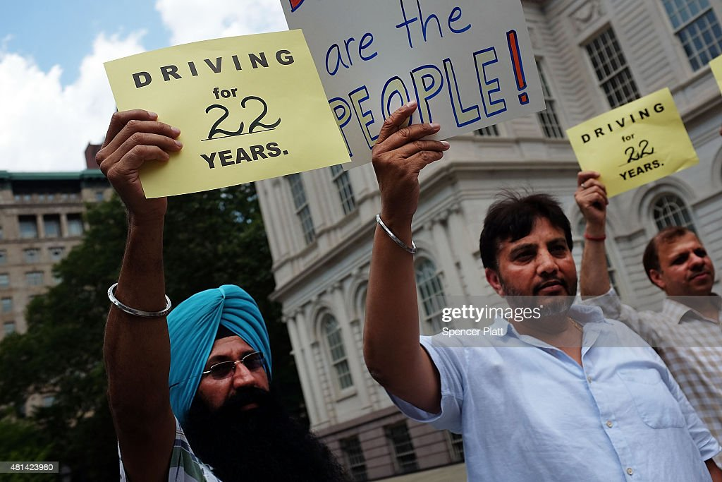 Taxi drivers, union members and civic groups hold a news conference and rally on the steps of City Hall to support a City Council move to limit the number of Uber drivers and other for-hire car companies on the streets of New York City on July 20, 2015 in New York City. New York's City Council has proposed two bills last month to limit the number of new for-hire vehicles, as well as to study the rapidly rising industry's impact on traffic. Uber has responded in an open letter arguing that its 6,000 Uber cars out during an average hour are a small part of the city's overall traffic. In cities across the globe Uber has upended the traditional taxi concept with many drivers and governments taking action against the California based company.