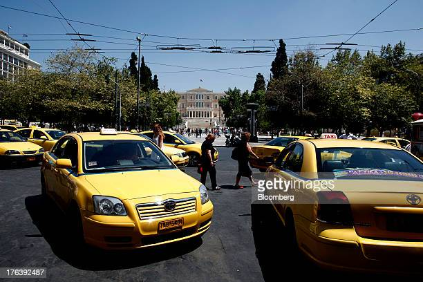 Taxi drivers wait for customers in their yellow cabs parked near the Greek national parliament center in Syntagma square in Athens Greece on Friday...