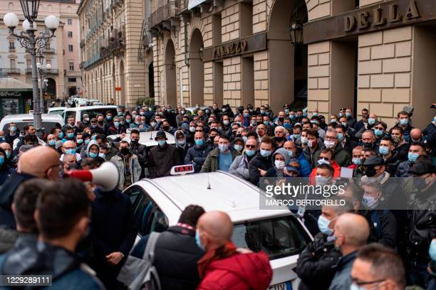 Taxi drivers wearing face masks stand next to taxis parked on Piazza Castello square in Turin, on October 26 during a strike to protest against...