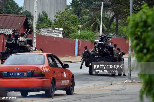 A taxi drives behind Ivorian soldiers as they patrol in their vehicle by Ivory Coast's army headquarters the Gallieni military camp in Abidjan on May...