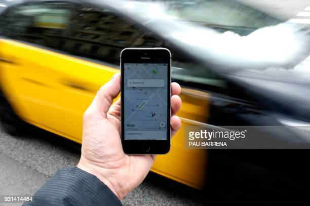 A taxi drives by a phone displaying the Uber app in Barcelona on March 13 2018 Uber said it was back in Barcelona with 120 professional drivers after...