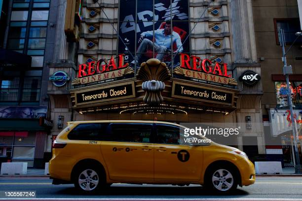 Taxi drives in front a Regal Cinema in Times Square on March 05, 2021 in New York City. NY Governor Andrew Cuomo permitted the reopening of movie...