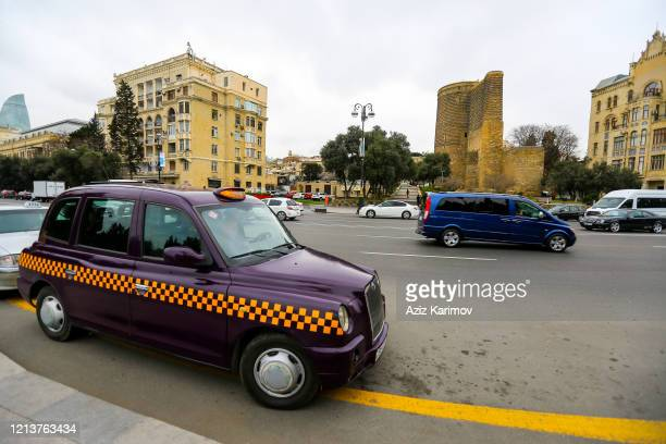 Taxi drives passed the Maiden Tower, also known as Giz Galasi, located in the Old City during the eve of Nowruz festival on March 20, 2020 in Baku,...