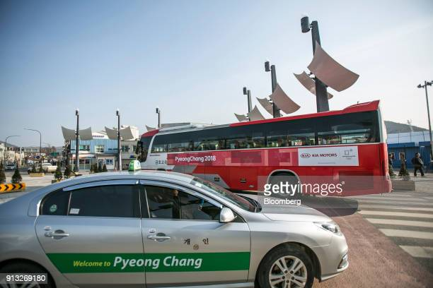 A taxi drives past a 2018 PyeongChang Winter Olympic Games shuttle bus manufactured by Kia Motors Corp in the Hoenggyeri village area of Pyeongchang...