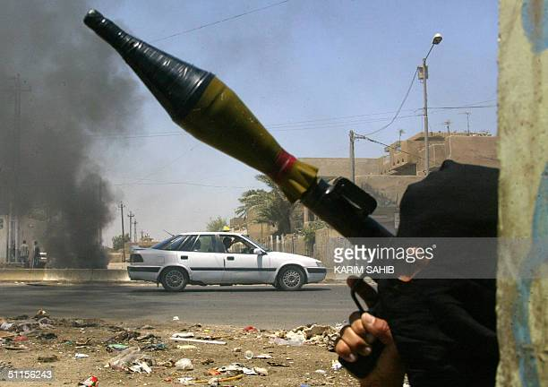A taxi drives past burning tires and a militiaman loyal to radical Iraqi Shiite Muslim cleric Moqtada Sadr armed with a grenade launcher in Baghdad's...