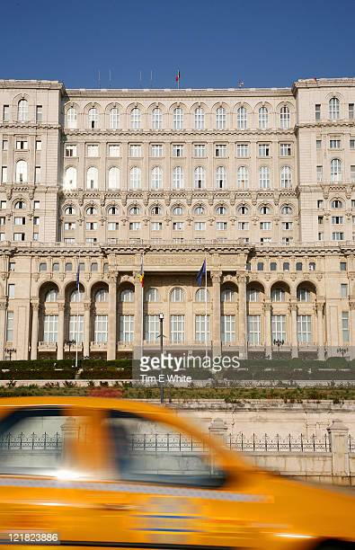 Taxi drives past the Palace of Parliament building, Bucharest, Romania