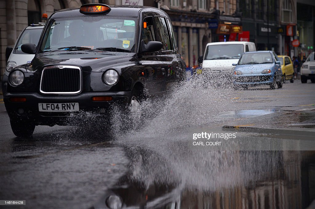 A taxi drives throgh a puddle left by persistent rain in central London on June 11, 2012. Persistent rainfall over much of southern England and the midlands has lead to the risk of flooding with the Met office issuing a severe weather warning.