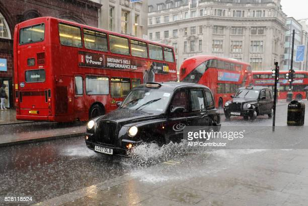 A taxi drives through a puddle past the city's iconic red buses as rain fell in central London on August 9 2017 / AFP PHOTO / Tolga AKMEN