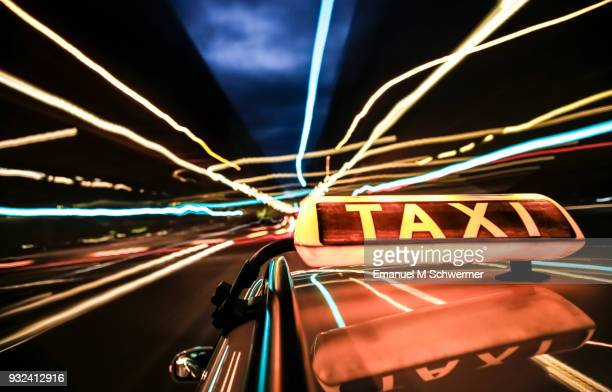 taxi drives through the city of berlin - taxi sign prominent in foreground - táxi - fotografias e filmes do acervo