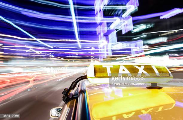 taxi drives through the city of Berlin - taxi sign prominent in foreground