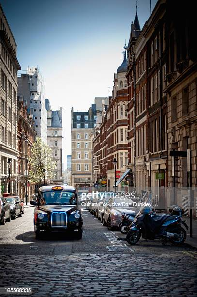 Taxi driving on cobbled London street