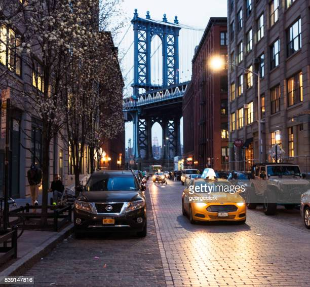 taxi in dumbo, brooklyn with the manhattan bridge behind - dumbo imagens e fotografias de stock