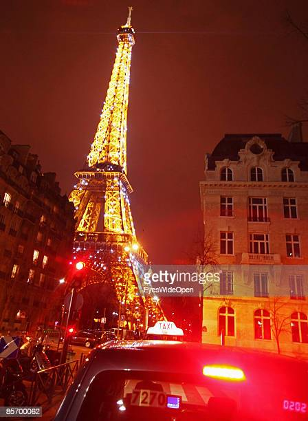 Taxi in front of the famous france landmark Eiffel Tower in Paris France on February 252009 The Eiffel Tower was built in 1886 by Gustave Eiffel with...