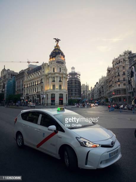 taxi en la gran vía de madrid al atardecer. españa - gran via madrid fotografías e imágenes de stock