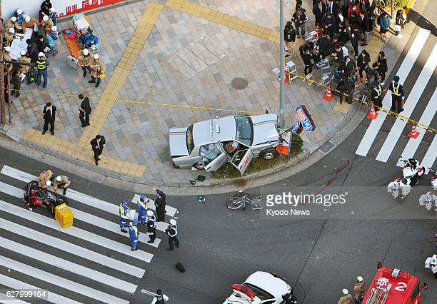 A taxi is seen smashed into a street light on a sidewalk at an intersection in Tokyo's Minamiaoyama district on Dec 6 after it ran into a bicycle and...