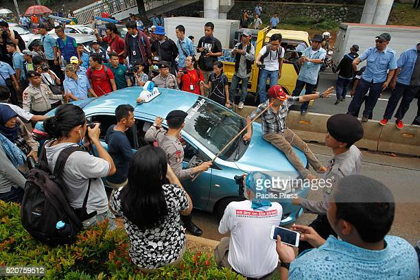 A taxi is stopped for not taking part in a protest by taxi drivers during a protest rally to demand the government to prohibit ridehailing apps