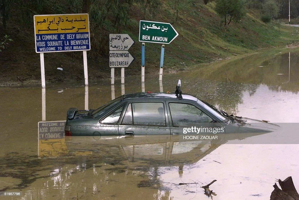 A taxi lies on a flooded road in Dely Ibrahim, nea : News Photo